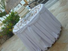 White linens and seashells wedding cake table Catillo Escondido Los Cabos