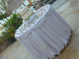 White linens and seashells wedding cake table Catillo Escondido Los Cabos